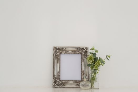 Picture frame, perfume bottle and flora on table