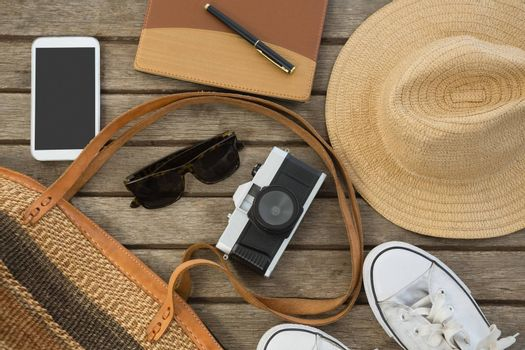 Overhead of travel accessories on wooden plank