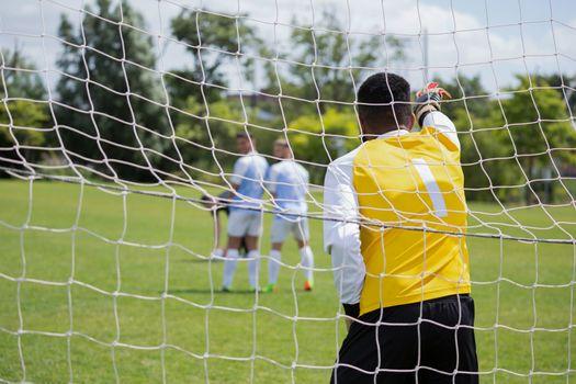 Goalkeeper standing at goal post
