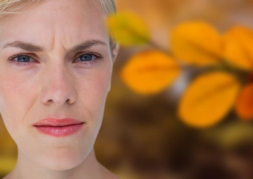 Concerned woman's face in forest with leaves