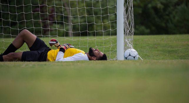 Goalkeeper relaxing near goalpost