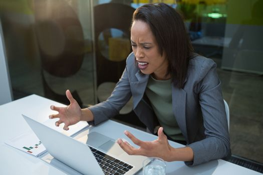 Irritated woman working at desk