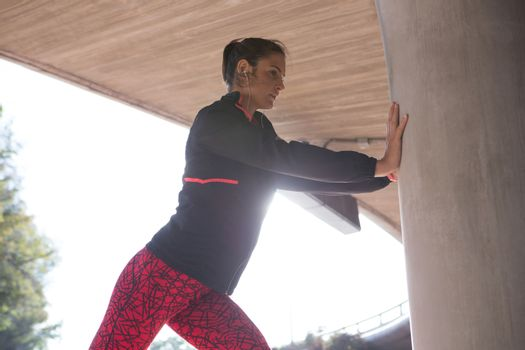 Fit woman doing stretching exercise with support of pillar