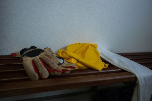 Gloves and football jersey on bench