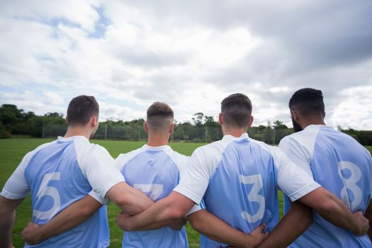 Football player standing together with arm around