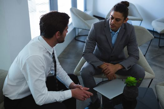 Businessmen interacting with each other in lobby