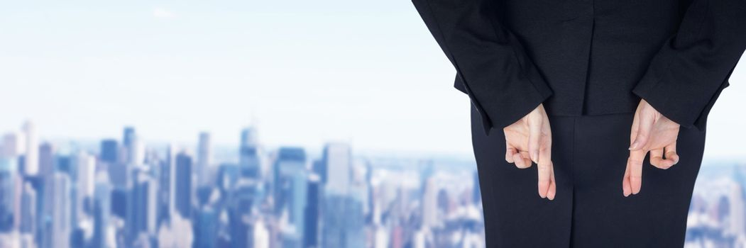 Businesswoman crossing fingers in city