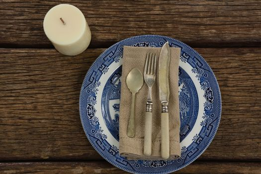 Cutlery and napkin on plate with candle