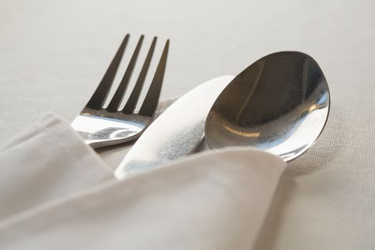 Spoon and fork wrapped in a napkin