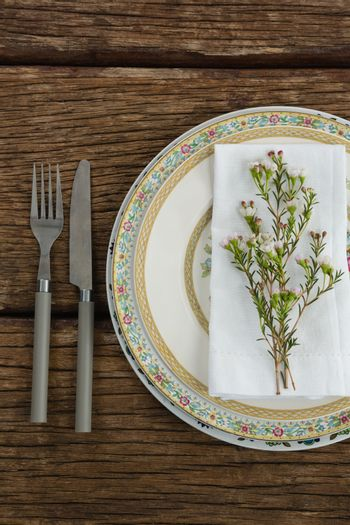 Flora and napkin arranged on plate with cutlery