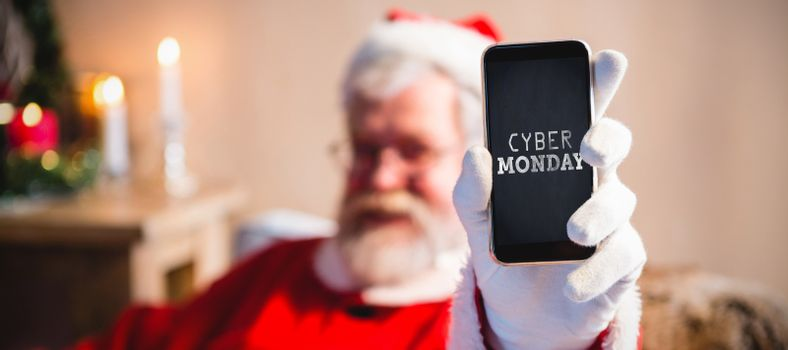Title for celebration of cyber Monday  against santa claus sitting and showing his smartphone