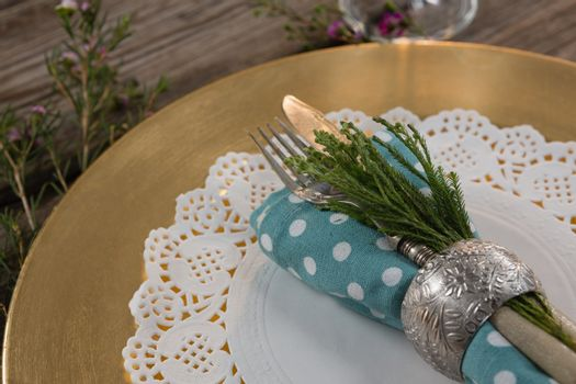 Folded napkin with cutlery and flora placed on palcemat
