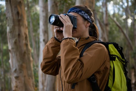 Hiker woman clicking a photo in forest