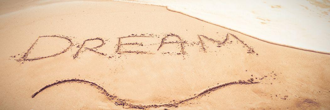 Inscription dream on sand