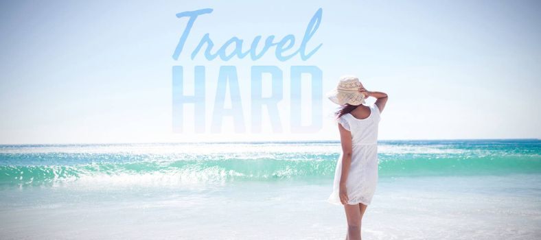 Travel hard against woman in straw hat at beach