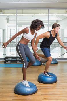 Couple doing aerobics on bosu balls