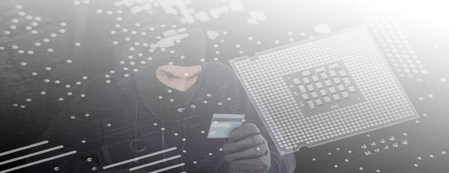 Composite image of focused burglar using computer and debit card