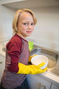 Boy washing utensil in kitchen