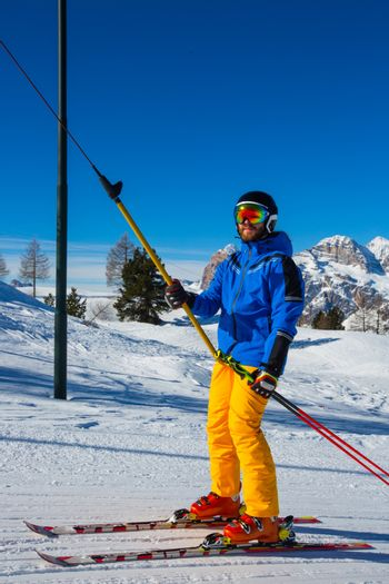Alpine skier with T-bar lift, blue and yellow clothes on slope with mountains in the background at Cortina d'Ampezzo Faloria skiing resort area Dolomiti Italy