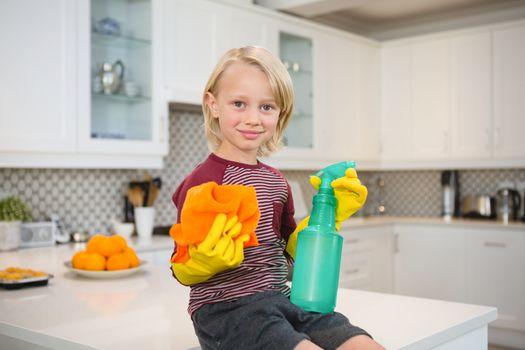 Boy holding rag and spray bottle in kitchen
