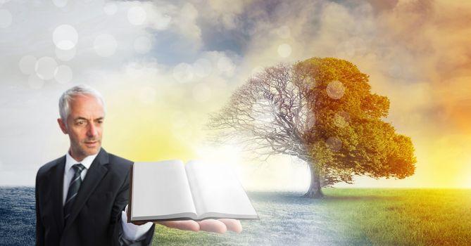 Man holding book with magical surreal seasonal tree imagination