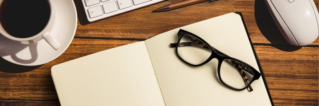 Notebook with glasses, coffee, keypad and computer mouse