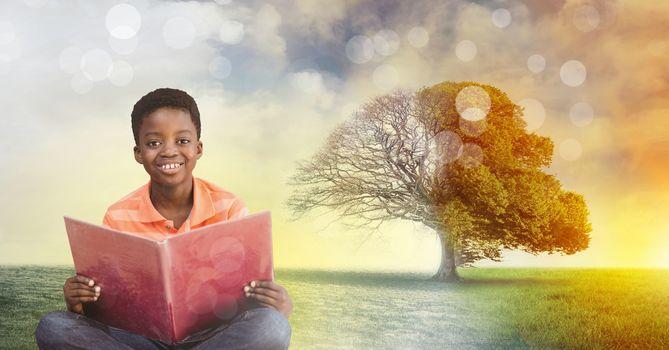 Boy holding book with magical surreal seasonal tree imagination