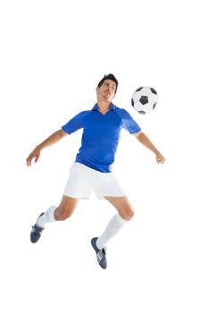 Fit player kicking football