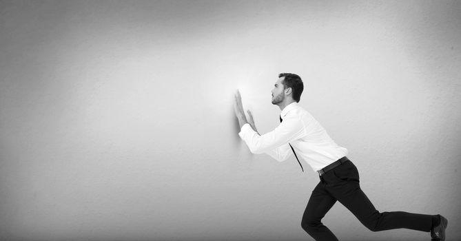 Businessman pushing against wall