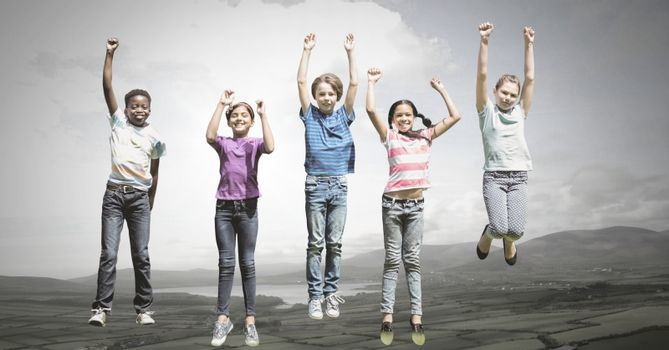 Children jumping for joy into sky with natural landscape