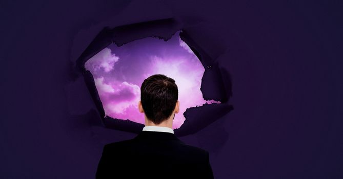 Businessman looking through through surreal paper hole