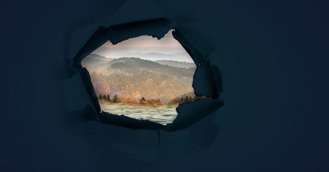 Nature landscape through surreal paper hole