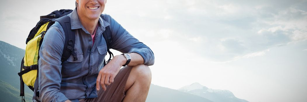 Composite image of portrait of confident male hiker crouching