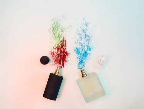 Flat lay composition with two perfume bottles with sparkles on paper background