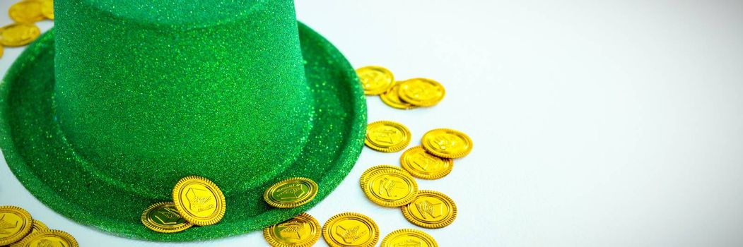 St. Patricks Day leprechaun hat and chocolate gold coins on white background