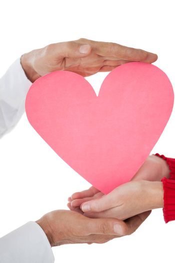 Close up of hands holding heart over white background