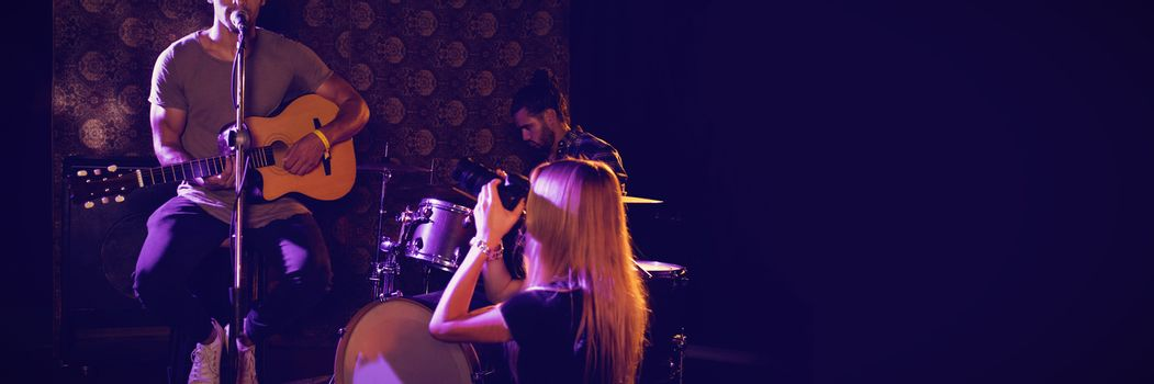 Woman photographing male performers in nightclub