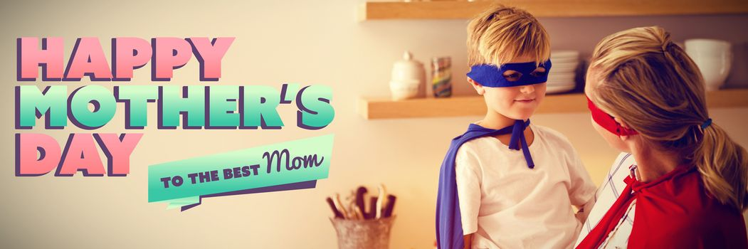 mothers day greeting against mother and son pretending to be superhero in the kitchen