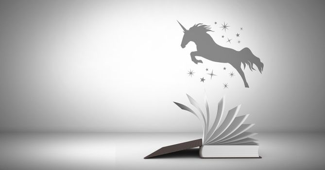Unicorn silhouette flying over magical book