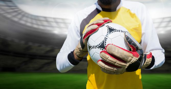 Goalkeeper holding football in stadium