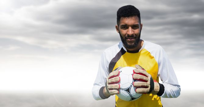 Goalkeeper holding football with clouds