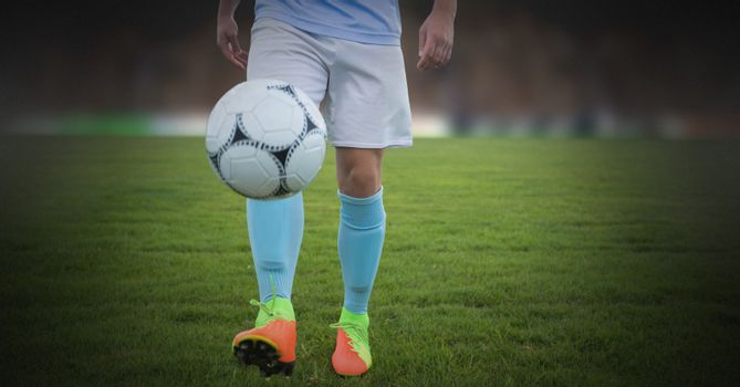 Soccer player on grass with football solo