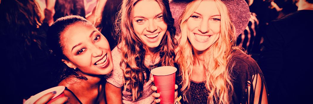 Female friends with disposable cups in club