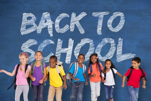 Elementary pupils running against blue chalkboard with back to school message