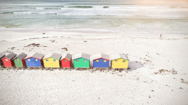 Multi colored wooden huts by mountain at beach