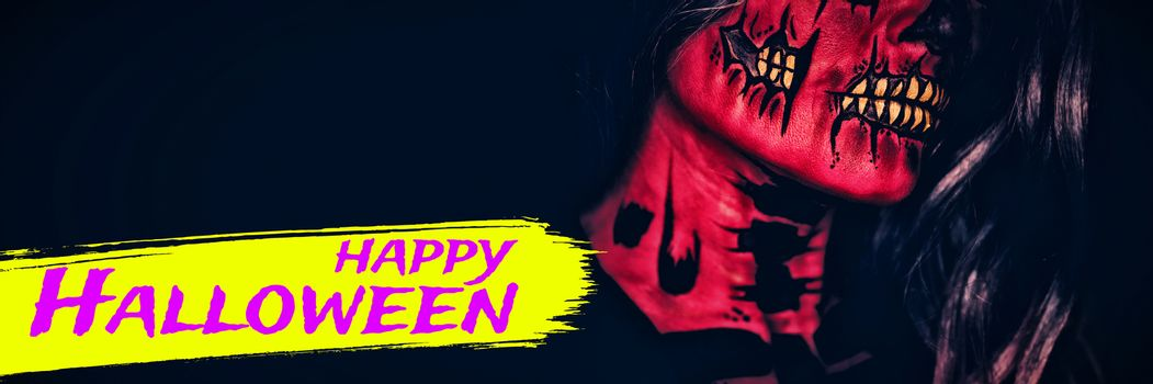Digital image of happy Halloween text against attractive young woman with halloween makeup
