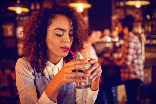 Young woman having red wine in pub