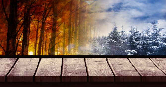 Digital composite of Autumn and Winter landscape seasonal weather transition with wood surface