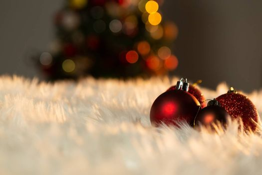 red Christmas balls on a white fur with a Christmas tree on the background