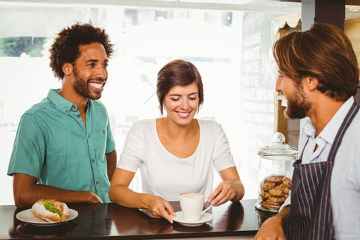 Barista talking with two customers